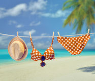 Beach outfit. Summer clothes set on tropical sea. Beach outfit. Summer clothes and accessories stylish set. Fashion swimsuit bikini red polka dots, sunglasses Stock Photos