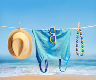Beach outfit. Summer clothes set on tropical sea. Beach outfit. Summer clothes and accessories stylish set. Fashion swimsuit, sunglasses, hat necklace on rope Stock Photography