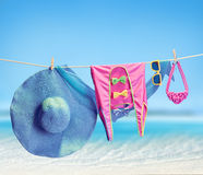 Beach outfit. Summer clothes set on tropical sea. Beach outfit. Summer clothes and accessories stylish set. Fashion swimsuit, sunglasses, hat and pareo on rope Stock Image