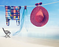 Beach outfit. Summer clothes set on tropical sea. Beach outfit. Summer clothes and accessories stylish set. Fashion swimsuit, sunglasses, hat and pareo on rope Royalty Free Stock Photos
