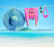 Beach outfit. Summer clothes set on tropical sea. Beach outfit. Summer clothes and accessories stylish set. Fashion swimsuit, sunglasses, hat and pareo on rope Stock Photo