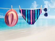 Beach outfit. Summer clothes set on tropical sea. Beach outfit. Summer clothes and accessories stylish set. Fashion swimsuit, sunglasses, hat on rope. Essentials Stock Image