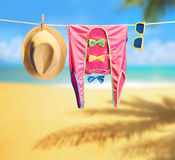 Beach outfit. Summer clothes set on tropical sea. Beach outfit. Summer clothes and accessories stylish set. Fashion swimsuit, sunglasses, hat on rope. Essentials Royalty Free Stock Photos