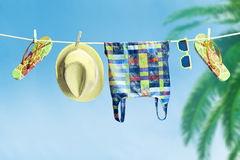Beach outfit. Summer clothes set on tropical sea. Beach outfit. Summer clothes and accessories stylish set. Flip flops, fashion swimsuit, sunglasses, hat on rope Royalty Free Stock Photo