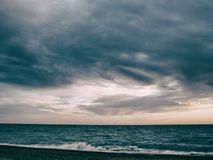 Beach, over the sea hanging storm cloud royalty free stock image