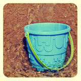 Beach pail in the sea. Picture of a blue beach pail in the sea, with a frame and a retro effect royalty free stock images