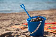 Beach Pail and Shovel. A blue pail full of sand on the beach Stock Image