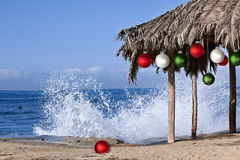 Beach Palapa Decorated For Christmas ~ Wave. Beach Palapa Decorated For Christmas Season ~ Red, White and Green Ornaments ~ Splashing Waves and Ocean Background Stock Photos