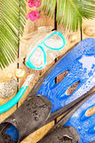 Beach, palm tree leaves, sand, fins, goggles and snorkel Royalty Free Stock Photos