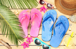 Beach, palm tree leaves, sand, sunglasses and flip flops. Summer holiday (vacation) tropical beach from above - palm tree leaves, exotic flowers, sunglasses and Stock Photos