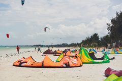 The beach with palm trees and kite laying on the ground and flying in the sky royalty free stock images