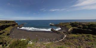 Beach panorama - Ocean, black sand, blue sky Stock Photos