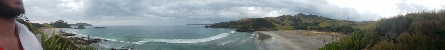 Beach panorama. Private bay of island beach campground called elliots bay panoramic with man Royalty Free Stock Image