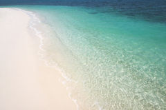 Beach Paradise. Clear blue water lapping gently on a white sandy beach on Rawa Island, Malaysia royalty free stock photo