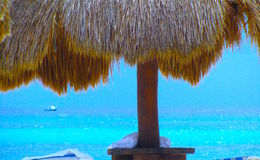 Grand Sirenis. Beach in Mexico,  never-ending blue ocean under a cloudless sky.  Shaded by a palapa by the luxurious resort Royalty Free Stock Photos