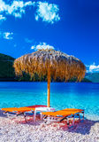Beach paradise. Two orange beach loungers and umbrella at tropical beach Royalty Free Stock Image