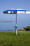 Beach parasol on green grass with blue sea in the background Stock Image