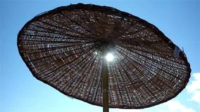 Beach parasol. Beach straw parasol moving in wind stock video footage