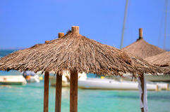 Beach parasols and boats Stock Photos
