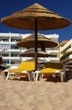 Beach parasols and lounge chairs. Two yellow beach chairs under a straw parasol on a sandy beach stock photography
