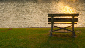 Beach in park. Vintage bench in public park with reflection of sunset on the lake effect, selective focus royalty free stock photos