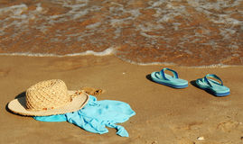 Beach party. A hat, a blue scarf and blue shoes left alone by a girl like an invitation to be followed into the sea Royalty Free Stock Photos