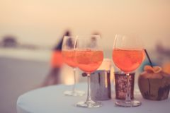 Beach party cocktail glasses on simple white table. Beach party background with drinks and blurred people in background Stock Photos