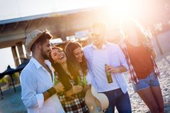 Beach party with friends. Cheerful young people spending nice time together on the beach royalty free stock photography