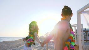 Beach party to waterfront slow motion, summer vacation in love on seacoast, flower wreaths on neck of young couple, stock footage