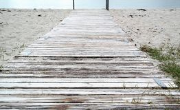 Beach path with planks, blue water with text space. Old planks on the beach, road to the water Royalty Free Stock Photos