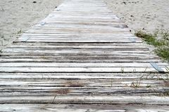 Beach path with planks, sand and textspace. Old planks on the beach Royalty Free Stock Photography