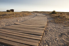 Beach path. A wooden pathway laid on the sand and going towards a cabin on a beach next to the sea. The picture was taken in the south of Spain (Andalusia), late Royalty Free Stock Image
