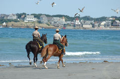Beach patrol 2. Two environmental officers on horseback patrolling the beach by the shoreline Stock Images