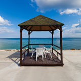 Beach pavilion with sky. Beach pavilion with white chairs and blue sky Royalty Free Stock Image