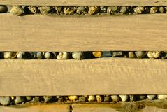 Pebbles stuck in the sea defence`s. Beach pebble`s wedged in the gaps between the boards on the sea defence`s Stock Images