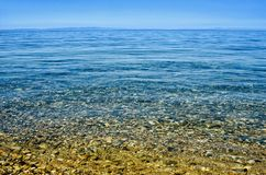 Beach with pebble and turquoise water under blue sky. Lake Baikal Royalty Free Stock Image