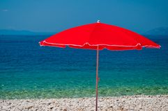 Beach with pebbles and red sunshade on a summer day Stock Photos