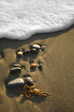 Beach Pebbles with Surf. Sandy beach and pebbles with surf foam Stock Photography
