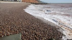 Beach with pebbles and waves low down view stock video footage