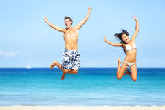 Beach people - happy couple jumping. In swimwear and bikini. Sunny summer travel image with young multiethnic couple on Hawaii, Big Island. Caucasian man, Asian stock images