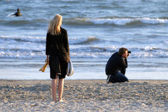 Beach Photographer. Photographer's Assistant Looks On at a Sunset Shoot Stock Images