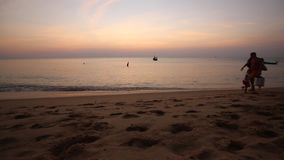 Beach at Phu Quoc island, Kien Giang province, Vietnam. People are walking on seashore at dusk, Phu Quoc island, Kien Giang province, Vietnam. Phu Quoc is stock footage