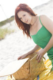 Beach picnic. A redhead at the beach with a picnic basket Royalty Free Stock Photos