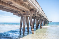 Beach Pier. Ocean side beach pier under brigh blue sky Royalty Free Stock Images