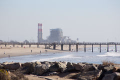 Beach with Pier and Power Plant and Jetty Royalty Free Stock Photography