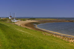 Beach with pier, sailboats and mudflats Royalty Free Stock Photos