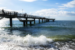 Beach pier in the sea waves against a blue sky on the Baltic Sea Stock Image
