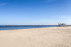 Beach and pier in a sunny day, space for text. Royalty Free Stock Image