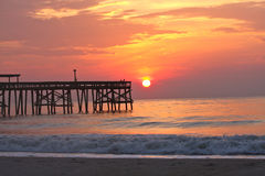 Beach with pier at sunrise Stock Image