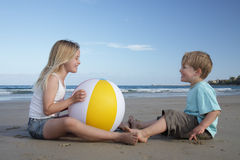 Beach play. A young girl and boy play with a beach ball at the beach Stock Photo